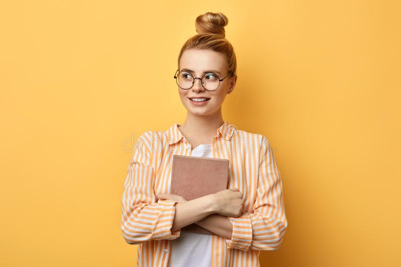 Happy young beautiful woman with hairbun standing and holding folder stock photo