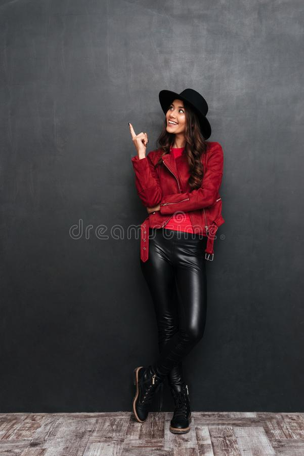 Happy young beautiful woman pointing. Looking aside. stock images