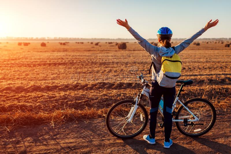 Happy young bicyclist raising opened arms in autumn field admiring the view. Woman feeling free. royalty free stock photo