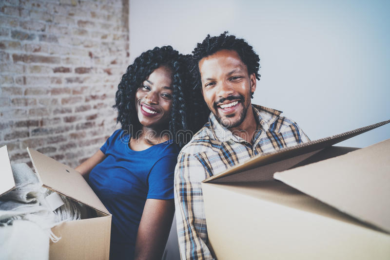 Happy young black african couple moving boxes into new home together and making a successful life.Cheerful family stock photography