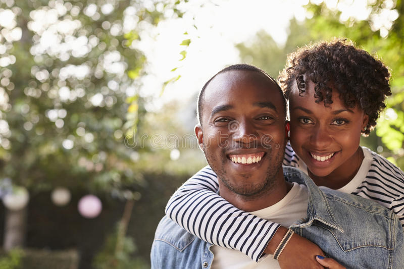 Happy young black couple piggyback in garden, look to camera royalty free stock photography