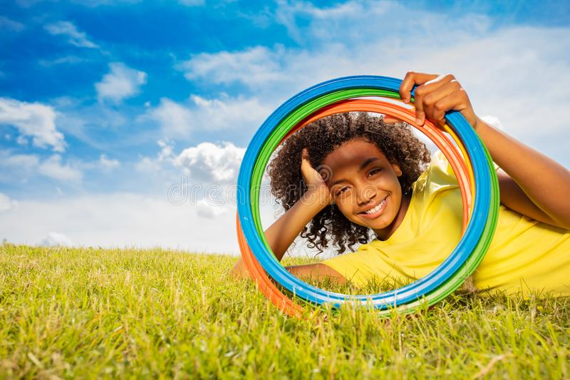 Happy young black girl looking through color hoops. Portrait of cute happy young black mixed-race girl looking through color hoops rings laying on grass lawn stock images