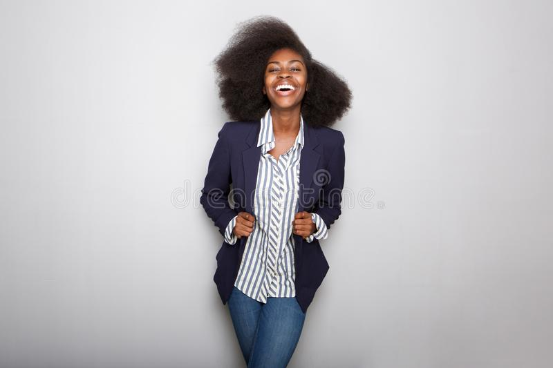 Happy young black woman with blazer against gray background stock photos