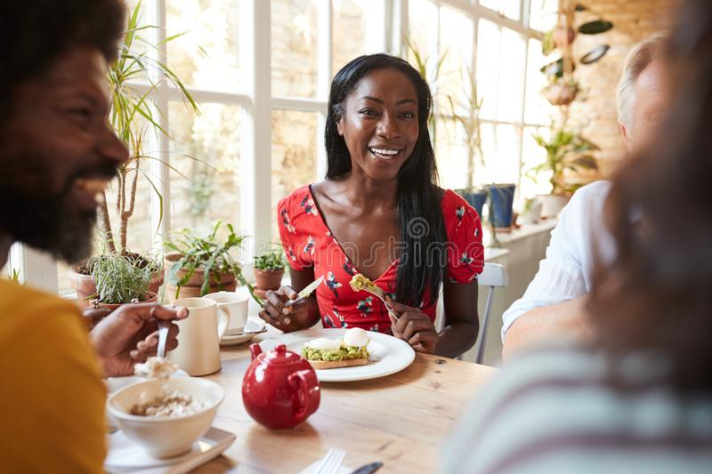 Happy young black woman eating brunch with friends at a cafe royalty free stock photos