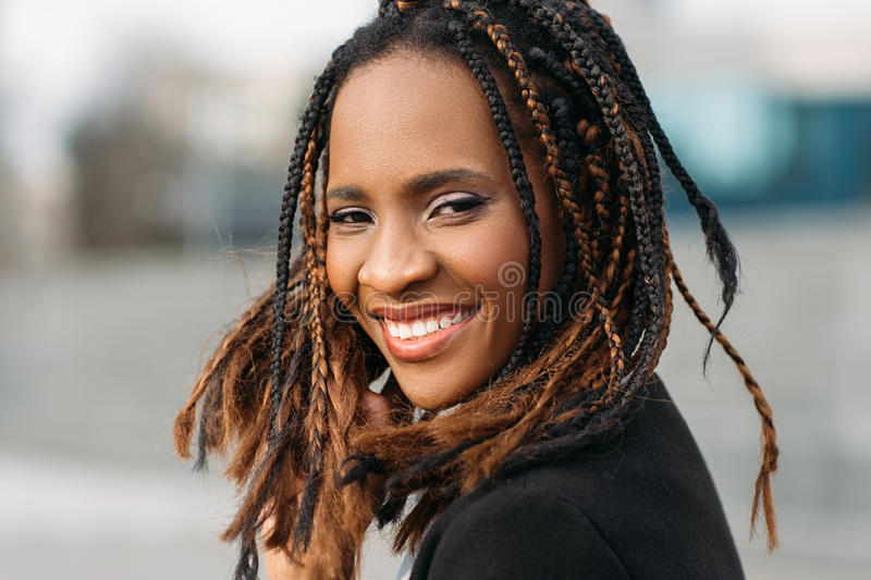 Happy young black woman. Joyful mood. Happy young black woman smile. Joyful mood. Stylish smiling model, African American female in selective focus outdoors royalty free stock image