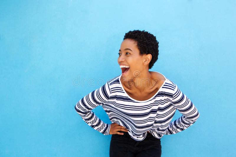 Happy young black woman laughing against blue background royalty free stock photos