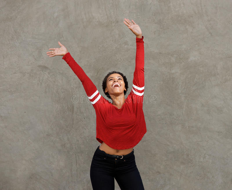 Happy young black woman laughing with arms raised stock photos