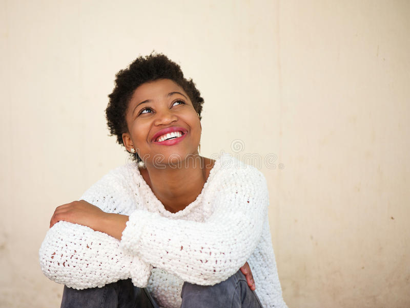 Happy young black woman smiling and looking up stock image