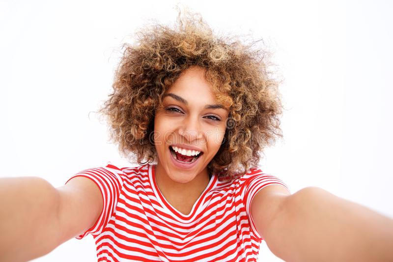 Happy young black woman taking selfie against white background. Portrait of happy young black woman taking selfie against white background stock images