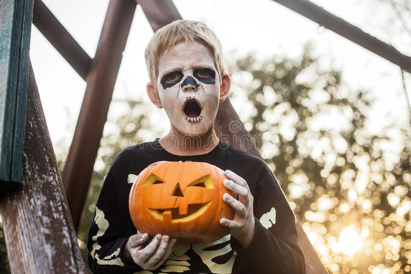 Happy young blond hair boy with skeleton costume holding jack o lantern. Halloween. Trick or treat. Outdoors portrait. Happy young blond hair boy with skeleton stock image