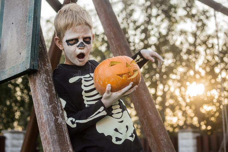 Happy young blond hair boy with skeleton costume holding jack o lantern. Halloween. Trick or treat. Outdoors portrait. Happy young blond hair boy with skeleton stock photography