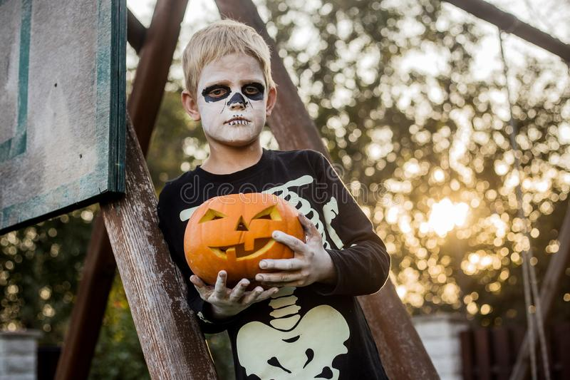 Happy young blond hair boy with skeleton costume holding jack o lantern. Halloween. Trick or treat. Outdoors portrait. Happy young blond hair boy with skeleton stock images