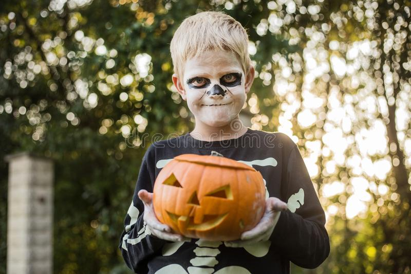 Happy young blond hair boy with skeleton costume holding jack o lantern. Halloween. Trick or treat. Outdoors portrait. Happy young blond hair boy with skeleton royalty free stock photos