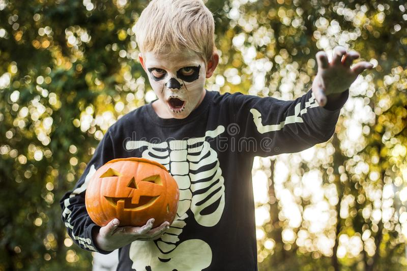 Happy young blond hair boy with skeleton costume holding jack o lantern. Halloween. Trick or treat. Outdoors portrait. Happy young blond hair boy with skeleton royalty free stock images