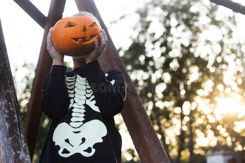 Happy young blond hair boy with skeleton costume holding jack o lantern. Halloween. Trick or treat. Outdoors portrait stock image