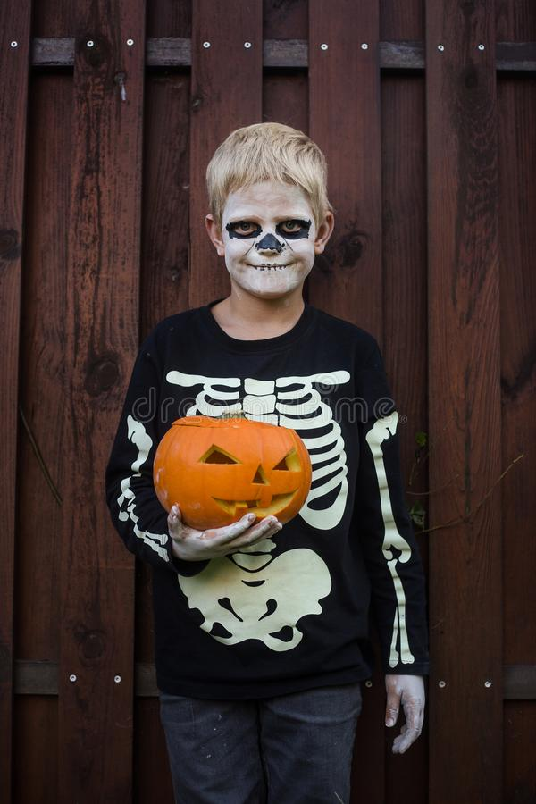 Happy young blond hair boy with skeleton costume holding jack o lantern. Halloween. Trick or treat. Outdoors portrait over wooden. Happy young blond hair boy royalty free stock photo