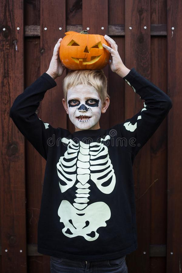 Happy young blond hair boy with skeleton costume holding jack o lantern. Halloween. Trick or treat. Outdoors portrait over wooden. Happy young blond hair boy stock photos