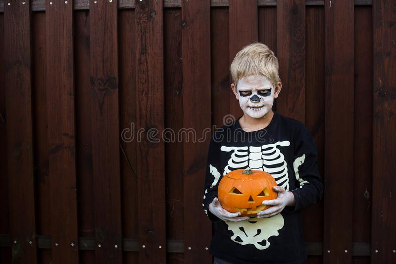 Happy young blond hair boy with skeleton costume holding jack o lantern. Halloween. Trick or treat. Outdoors portrait over wooden. Happy young blond hair boy stock image
