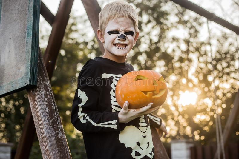 Happy young blond hair boy with skeleton costume holding jack o lantern. Halloween. Trick or treat. Outdoors portrait. Happy young blond hair boy with skeleton stock photo