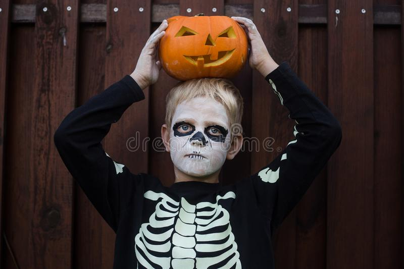 Happy young blond hair boy with skeleton costume holding jack o lantern. Halloween. Trick or treat. Outdoors portrait over wooden. Happy young blond hair boy royalty free stock photos