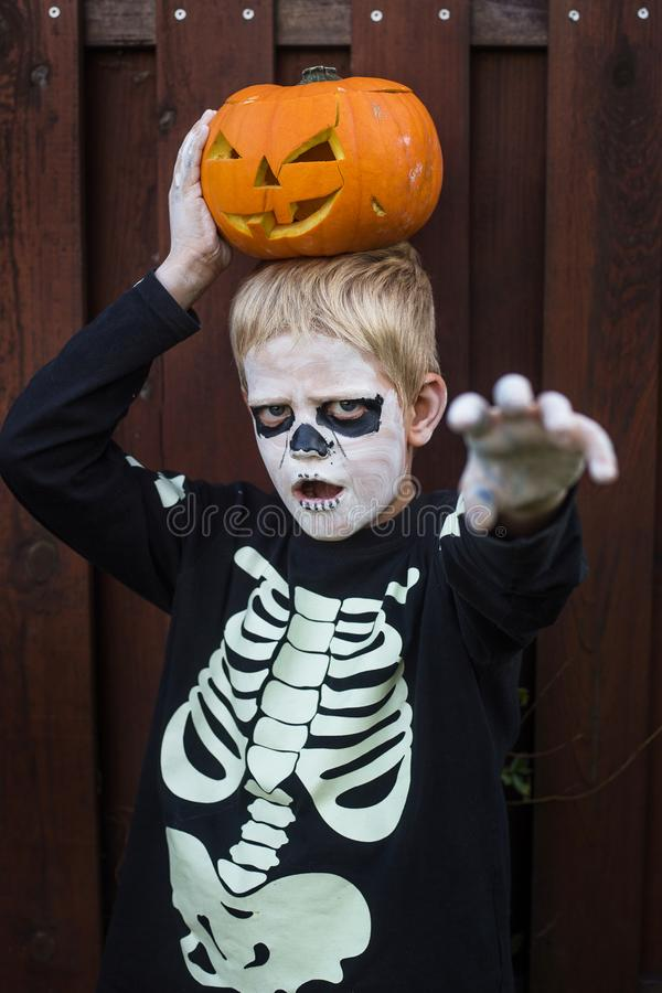Happy young blond hair boy with skeleton costume holding jack o lantern. Halloween. Trick or treat. Outdoors portrait over wooden. Happy young blond hair boy stock images
