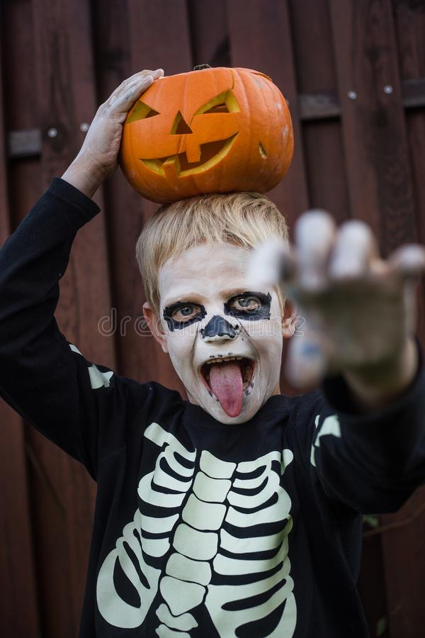 Happy young blond hair boy with skeleton costume holding jack o lantern. Halloween. Trick or treat. Outdoors portrait over wooden. Happy young blond hair boy royalty free stock photography
