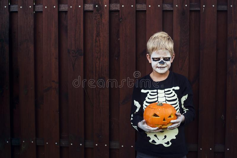 Happy young blond hair boy with skeleton costume holding jack o lantern. Halloween. Trick or treat. Outdoors portrait over wooden. Happy young blond hair boy royalty free stock image