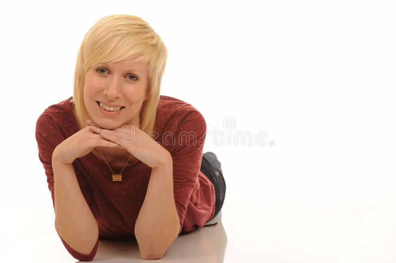 Happy young blond woman. Portrait of happy young blond woman lying on white studio background resting chin on hands royalty free stock photography