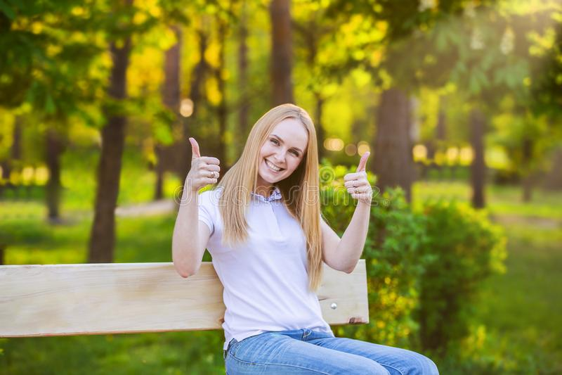 Happy young blond woman giving thumbs up on a green sun background stock images
