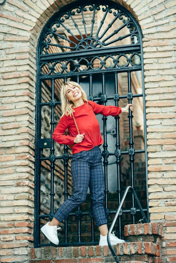 Happy young blond woman next to urban door. royalty free stock photos