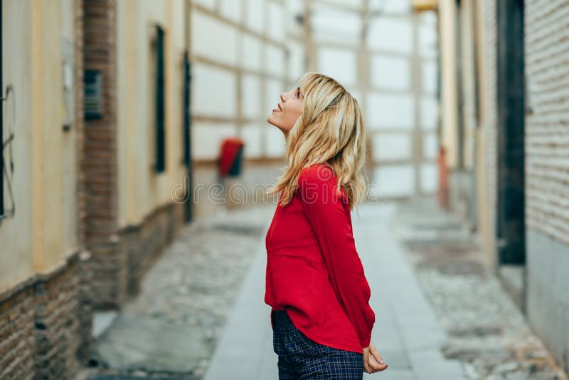 Happy young blond woman walking down the street royalty free stock image
