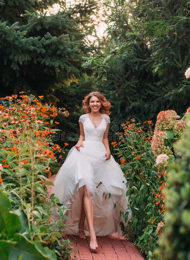 Happy young blonde girl in an elegant amazing long white wedding light dress with a long train, walking in a wonderful. Garden barefoot and laughs at the camera royalty free stock photo