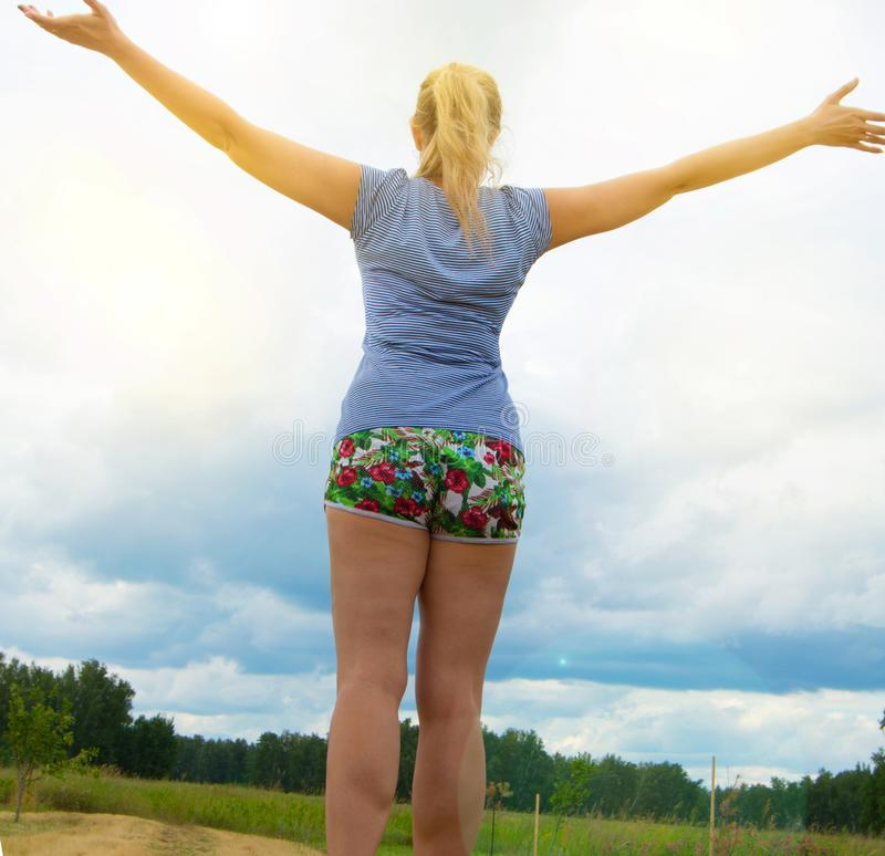 Happy young blonde wearing shorts and a t-shirt stands on the road against the sky with her arms outstretched, illuminated by. Sunlight on a summer day royalty free stock photos