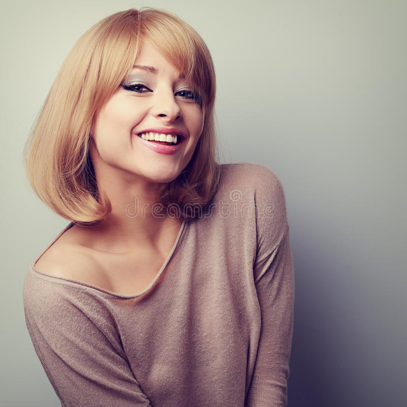Happy young blonde woman in fashion blouse laughing. Vintage closeup portrait royalty free stock photos