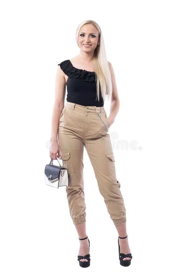Happy young blonde woman with handbag wearing military ocker pants posing stock photography