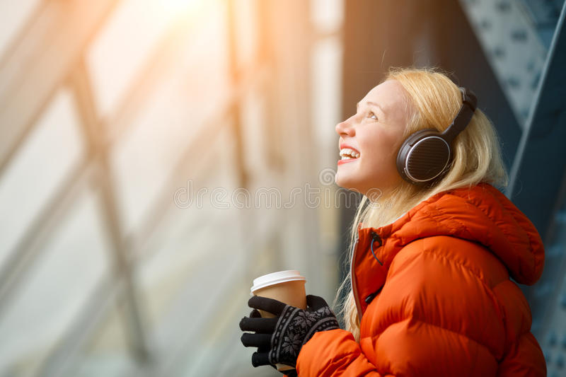 Happy young blonde woman in headphones holding coffee in hands royalty free stock photography