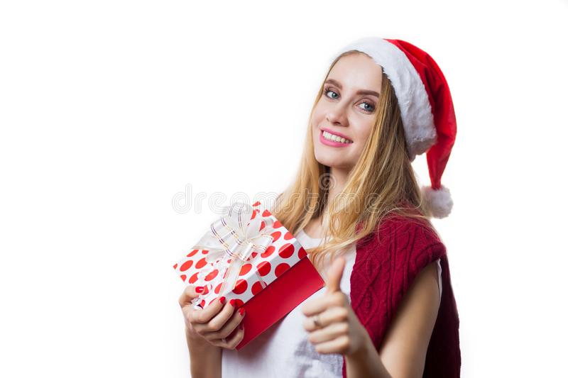 Happy young blonde woman holding a gift box on her hand and showing thumb up on white background stock photo