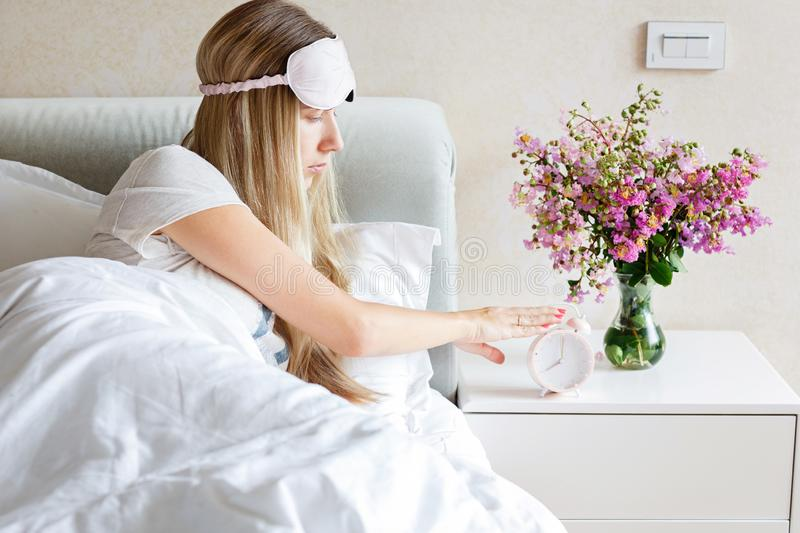 Happy young blonde woman in pajamas and blindfold waking up and turning off the alarm clock having a good day. Morning stock photo