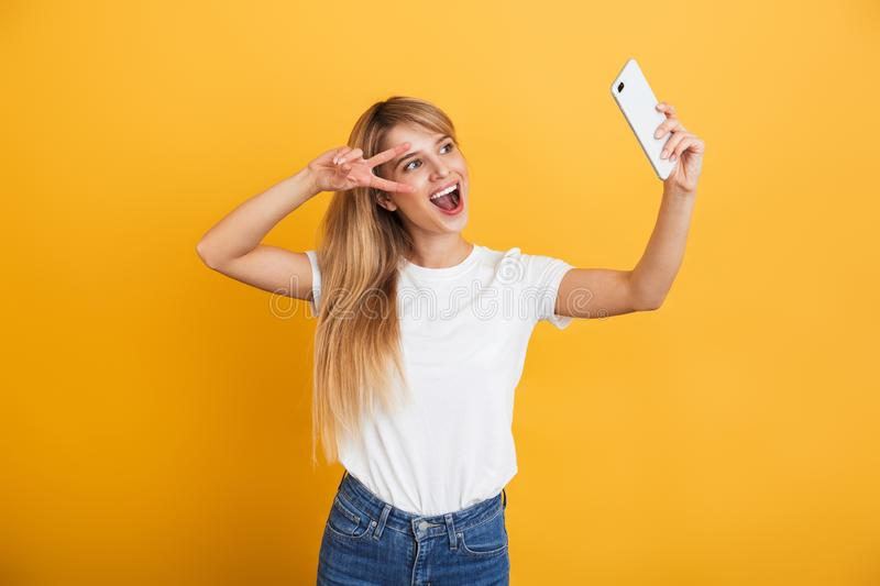 Happy young blonde woman posing isolated over yellow wall background dressed in white casual t-shirt using mobile phone take a royalty free stock photos