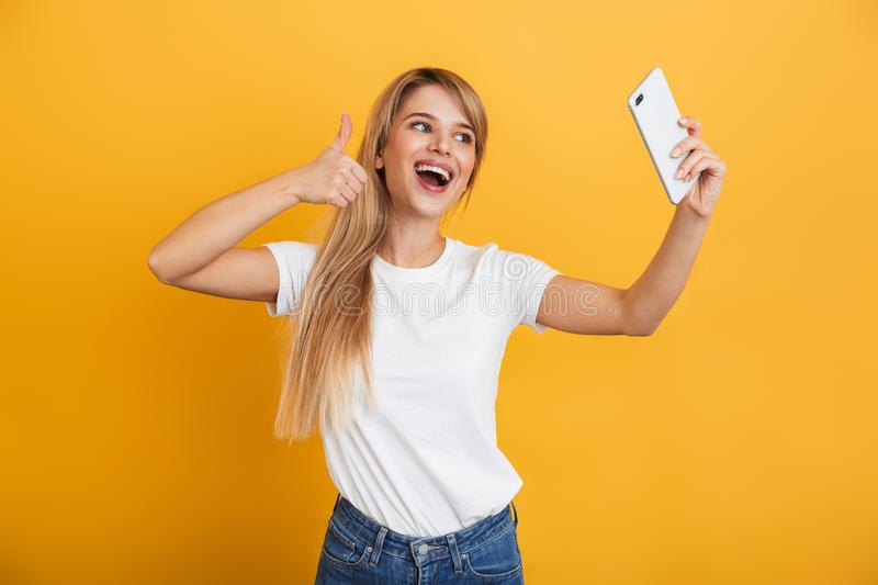 Happy young blonde woman posing isolated over yellow wall background dressed in white casual t-shirt using mobile phone take a stock photos