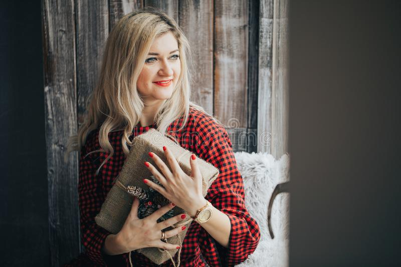 Happy young blonde woman in a red sweater received a gift for Christmas, new year, the girl smiles and holds a gift box stock photo