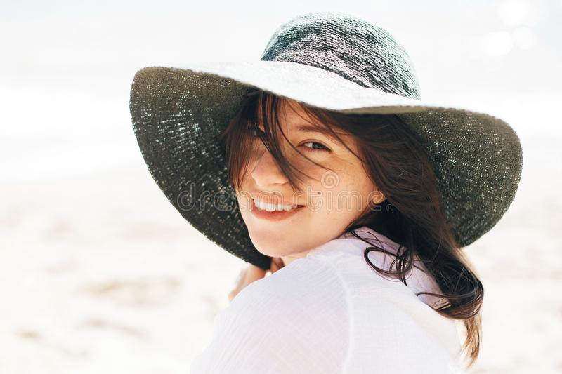 Happy young boho woman in hat relaxing and enjoying sunny warm day at ocean. Space for text. Stylish hipster girl sitting on beach. And tanning. Summer vacation royalty free stock image