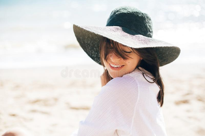 Happy young boho woman in hat relaxing and enjoying sunny warm day at ocean. Space for text. Stylish hipster girl sitting on beach. And tanning. Summer vacation royalty free stock images