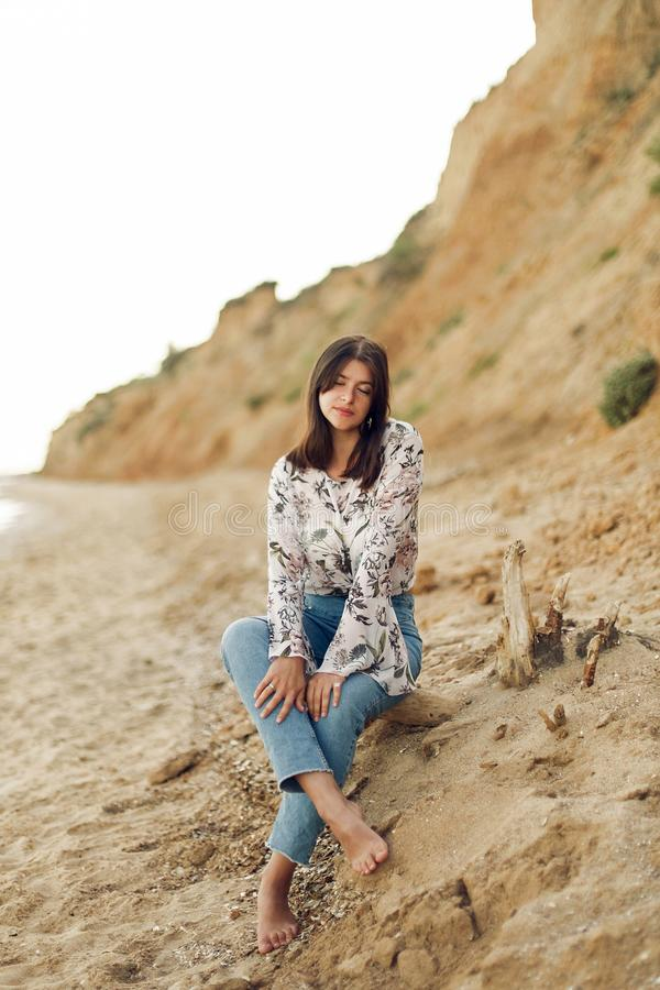 Happy young boho woman sitting and relaxing on sunny beach with rock. Hipster bohemian carefree girl smiling at sea. Summer stock photos