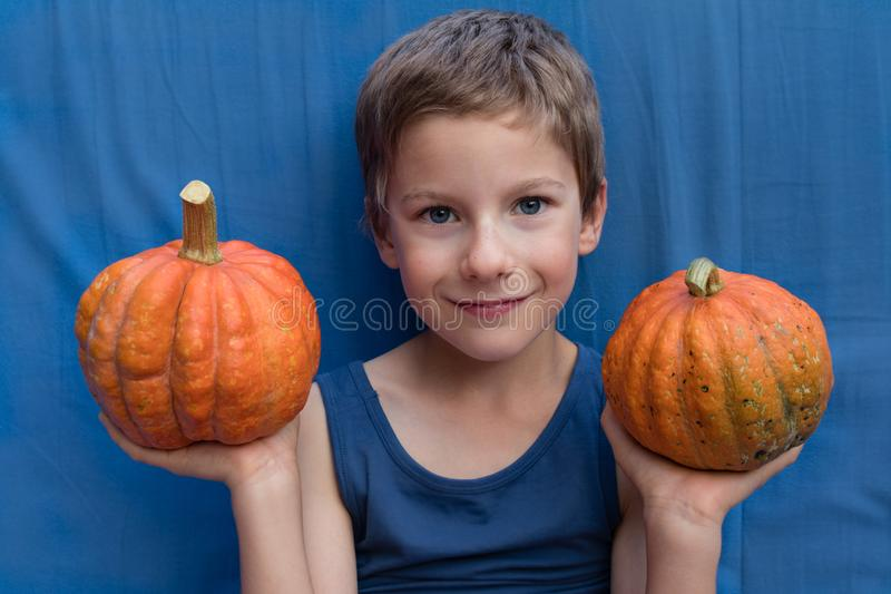 Happy young boy on the blue background with pumpkins. Colorful Halloween or Healthy Lifestyle design.  royalty free stock image