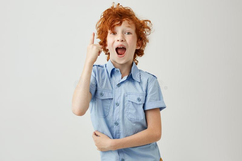 Happy young boy with curly ginger hair and freckles in blue shirt pointing upside with happy and excited expression stock photo