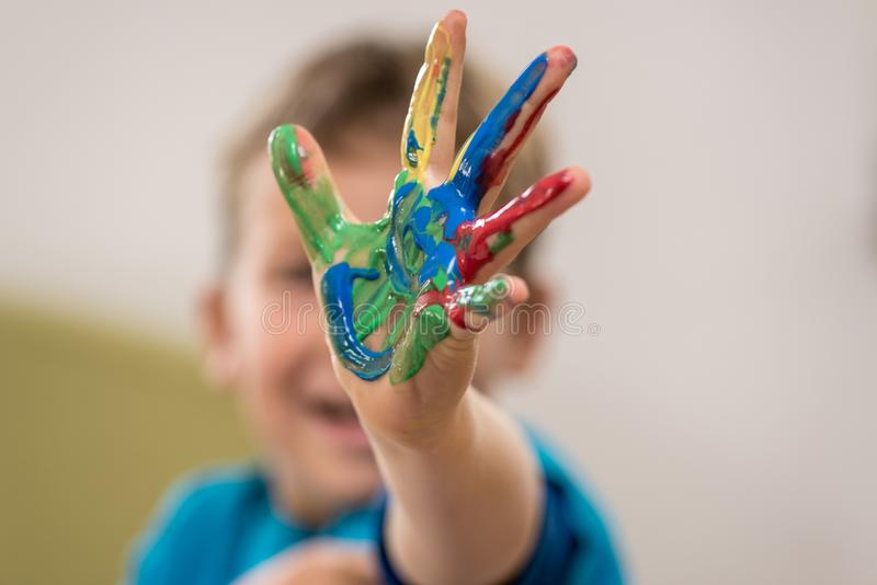Happy young boy doing hand painting stock image