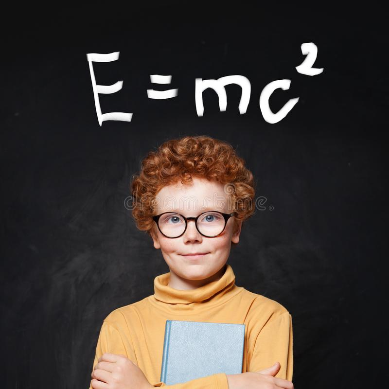 Happy young boy genius and science formula against chalkboard stock image