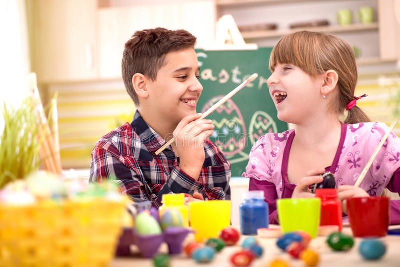 Happy young boy and girl playing with Easter eggs. Two smiling kids in home kitchen with easter eggs stock image