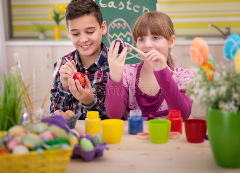 Happy young boy and girl playing with Easter eggs. Two smiling kids paint easter eggs royalty free stock photography
